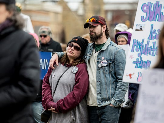 Ashley Spratt and Daniel Criss listen as students from Newark High School speak during the March for our Lives protest in front of the Licking County Courthouse.
