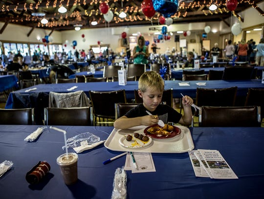 Alex Wyler, 6, digs into his pizza and meatballs while