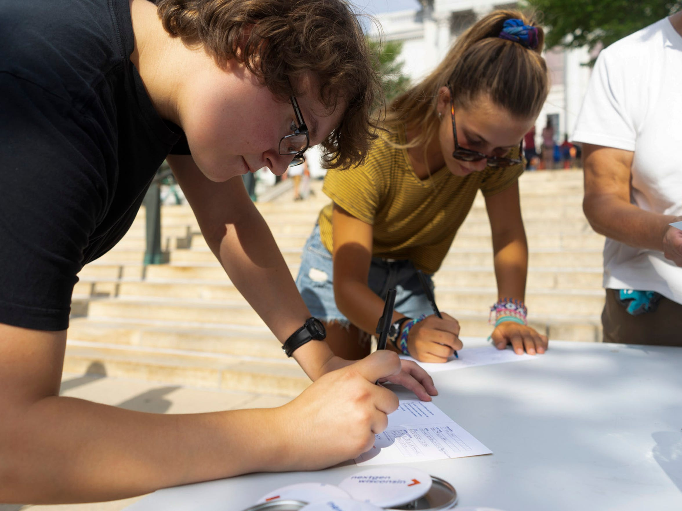 Frances Bartolutti, 19, at left, and Talia Glass pledge to vote at a table run by political advocacy group NextGen America at the Wisconsin State Capitol on Aug. 4. Bartolutti says she was looking forward to voting in her first Senate and gubernatorial race. A government study found that voter ID requirements such as Wisconsin's can lead to lower voter turnout among young people.