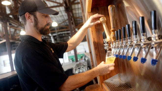 Alan Dritenbas, co-owner of Walking Tree Brewery in Vero Beach, draws a draught.