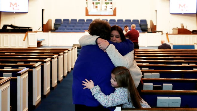 Ashley King, an aide at Marshall County High School and who heard the gunfire that killed two students and wounded 19, hugs mother Debbie Styre with daughter Kiley, 8, before the start of a prayer vigil in Benton, Ky.
