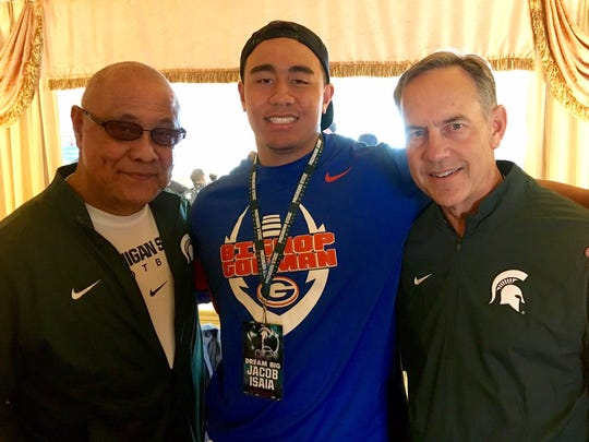 Mark Dantonio, right, is targeting offensive lineman Jacob Isaia for Michigan State's 2018 recruiting class. Isaia, middle, is the grandson of Spartan legend Bob Apisa, left.