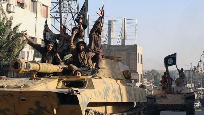 Fighters from the Islamic State ride tanks during a parade in Raqqa, Syria, in this undated image.