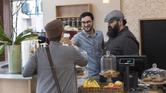 General Manager LJ Lara, right, and John Leyvas serve Dina Restivo in the new Tazz.Coffee. The new business opened on the southwest corner of Main and West streets on Monday, February 6, 2017.