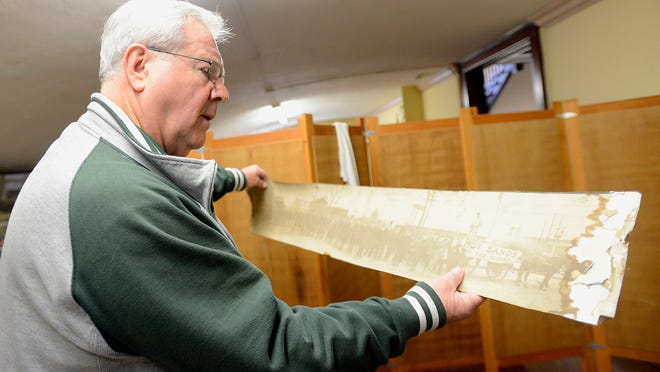 Ron Hannold holds up an old photograph from the turn of the century in the Charlotte Masonic Temple. Hannold, a Mason himself, is building manager of the Masonic Temple in Charlotte where the first floor will be renovated into apartments.