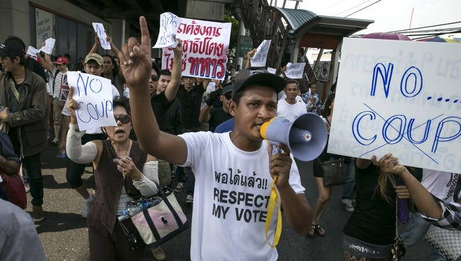 Protesters hold signs during an anti-coup protest on the second day of Thailand's military coup May 24, 2014, in Bangkok.