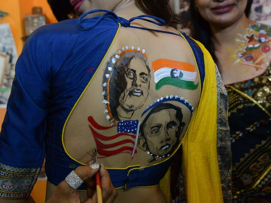 Indian tattoo artist Jagruti Parmar paints portraits of President Barack Obama and Indian Prime Minister Narendra Modi onto the back of a model at her studio in Ahmedabad on Friday, Sept. 26, 2014, in commemoration of Modi's visit to the U.S. The official visit is focused on boosting trade and resetting ties with the world's largest economy.