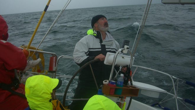 Boat owner Chuck Blaty checks the main sail while manning the wheel during a storm on Lake Huron.