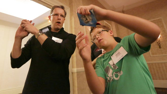 Magician Kirk Patrick of Oak Creek shows a card move to Geno Ploeger, 11, of Hartland, Wis., on Saturday at the Radisson Paper Valley Hotel in Appleton where the Houdini Club of Wisconsin held its 77th annual convention. The club held contests and workshops in Appleton with public performances at UW-Fox Valley in Menasha.