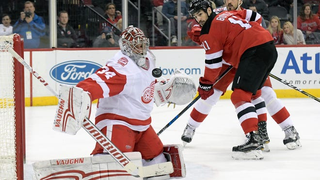 Red Wings goaltender Petr Mrazek (34) deflects the puck as Devils center Brian Boyle (11) looks on during the second period of the Wings' 3-0 win on Monday, Jan. 22, 2018, in Newark, N.J.