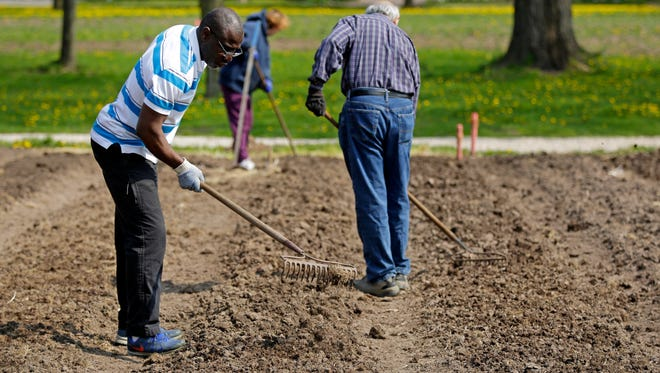 Members of St. Bernard Parish and the Fox Valley Islamic Society conclude an eight-week study program to learn more about each other's faiths. Mamadou Coulibaly, left, Mohammad Rashid and Linda Adams were among those doing volunteer work Saturday at Riverview Gardens in Appleton.