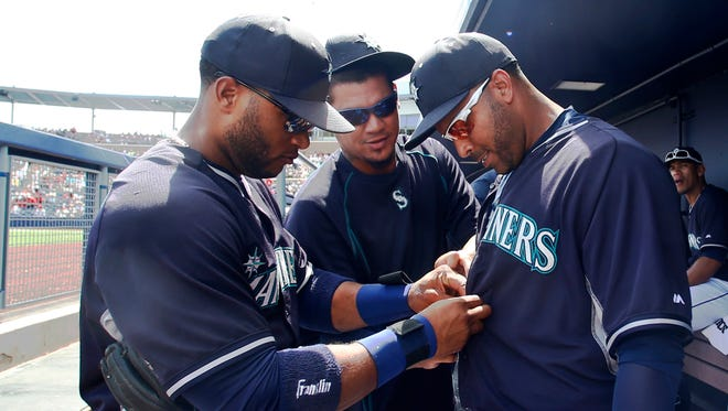 Seattle Mariners' Robinson Cano, left, and Felix Hernandez, center, take charge of the wardrobe work on teammate Nelson Cruz prior to the start of a spring training baseball game against the Los Angeles Angels Monday, March 30, 2015, in Peoria, Ariz.