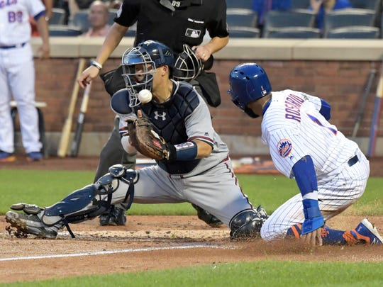New York Mets' Amed Rosario scores on a single by Jacob deGrom as Atlanta Braves catcher Kurt Suzuki cannot handle the throw during the third inning of a baseball game Friday, Aug. 3, 2018, in New York.