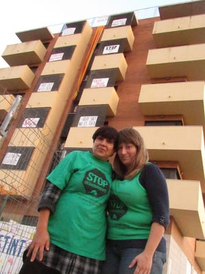 Clad in the green shirts of the Mortgage Victims' Platform, Doris Perez and Marta Afuera Pons stand in front of Bloc Salt.
