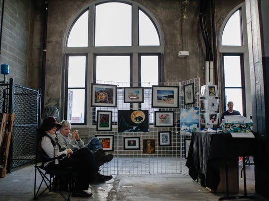 Sarah Rocheleau and Richard Uber, of Rocheleau Art, sit with their display of framed art inside Rhinegeist during Art on Vine Sunday.