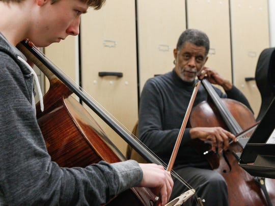 Norman Johns, CSO cellist, plays along on his own cello with student Mason Damaska, 17,  during a class at the School for Creative and Performing Arts.