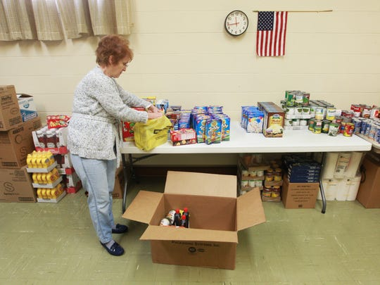 Sue Taylor unloads a box of food from a donation by Dollar General on Tuesday.