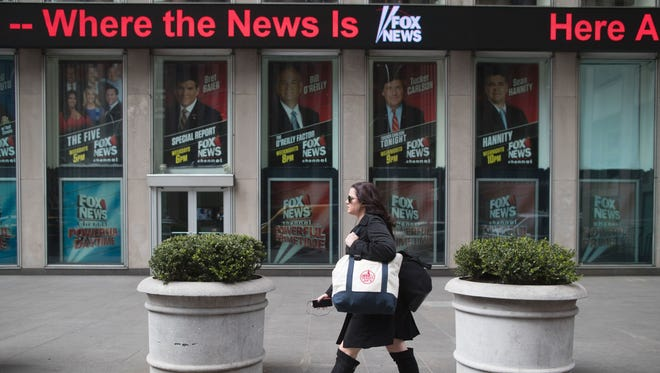 A woman walks past the News Corp. headquarters building displaying posters featuring Fox News Channel personalities including  Bill O'Reilly, top center, in New York, on April 19, 2017.