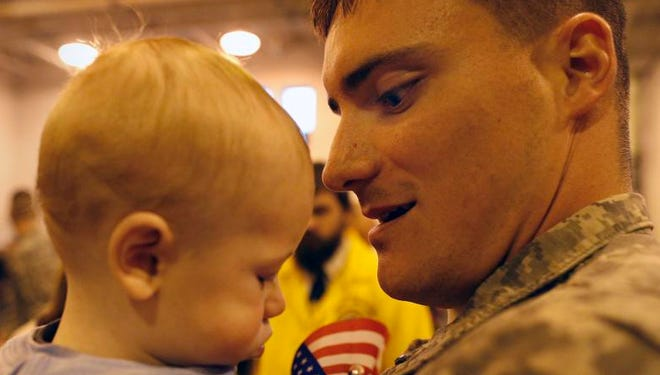 Stephen Mulholland of Auburn holds his son Carter, 6 months, for the first time since Carter was eight days old. Mullholland's company, the 222nd Military Police Company, returned to Rochester on Saturday.