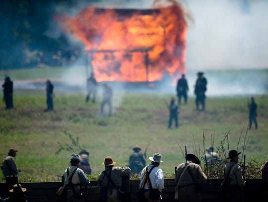 Confederate re-enactors look on from their fortification