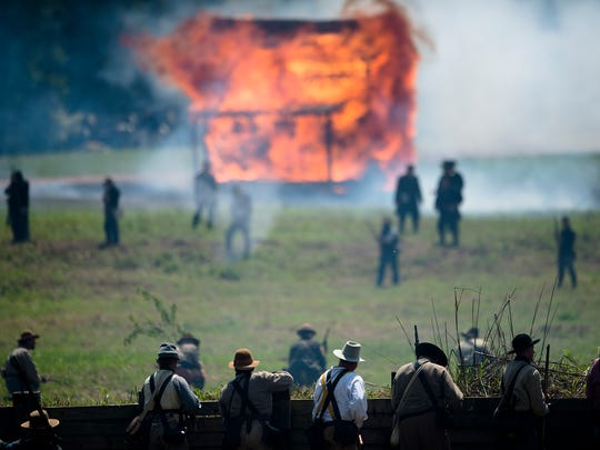 Confederate re-enactors look on from their fortification as Union re-enactors burn a building while they perform a re-enactment of the Battle of Selma on Sunday, April 26, 2015, in Selma, Ala. This years re-enactment marked Battle of Selma's 150th anniversary. The Battle of Selma occurred during the the Civil War in 1865.