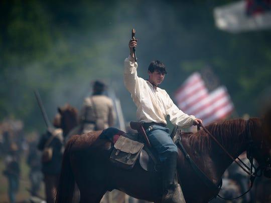 A Confederate re-enactor surrenders to Union re-enactors