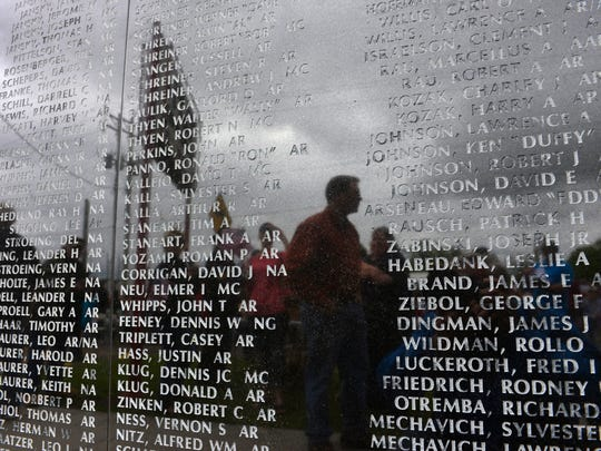 Attendees look over the names etched on the veterans monument wall outside the St. Cloud Granite VFW Post 428.