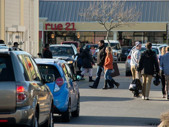 A steady stream of shoppers and cars flow through the