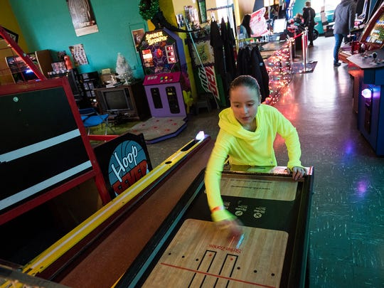 Hailey Bosworth, 13, of Dover, plays an air table bowling game at Timeline Arcade while with her family the day after Christmas Dec. 26, 2015 in downtown Hanover.