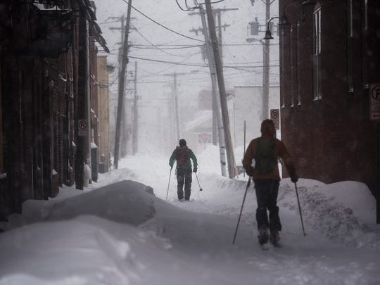 A pair of skiers make their way down an alley in downtown Hanover, Pa. on Saturday Jan. 23, 2016.