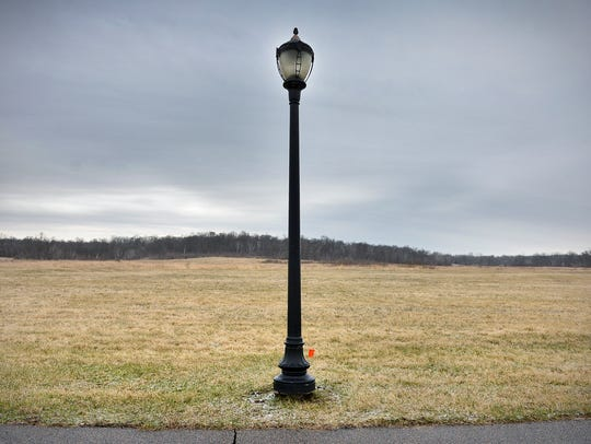 A light pole sits at the edge of the land for a proposed
