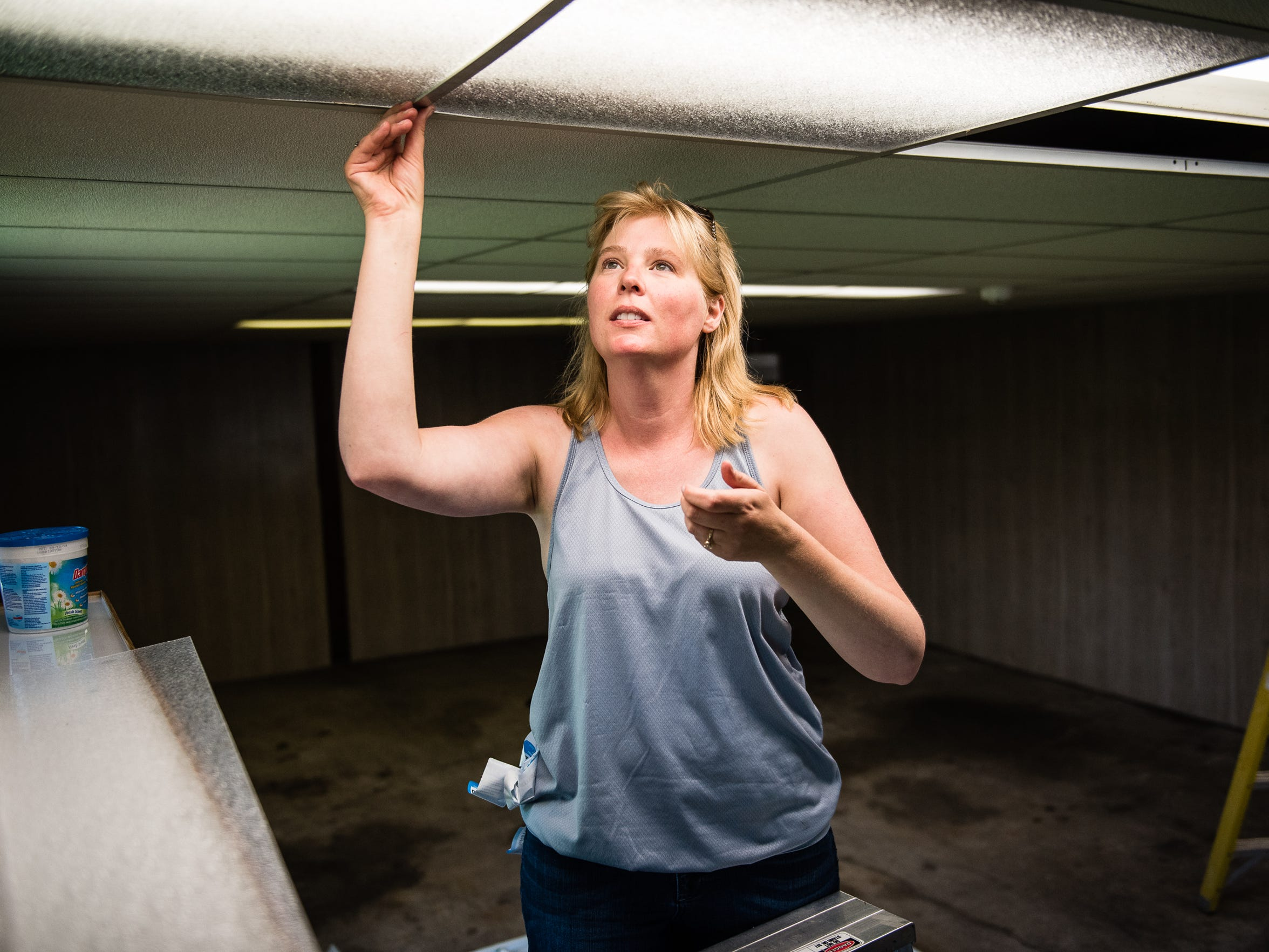 Kirsten Schaub of Hanover works on ceiling light fixtures at a warehouse in Hanover that will be used as the headquarters for Love LIVES, a non-profit that aims to help victims of domestic violence.