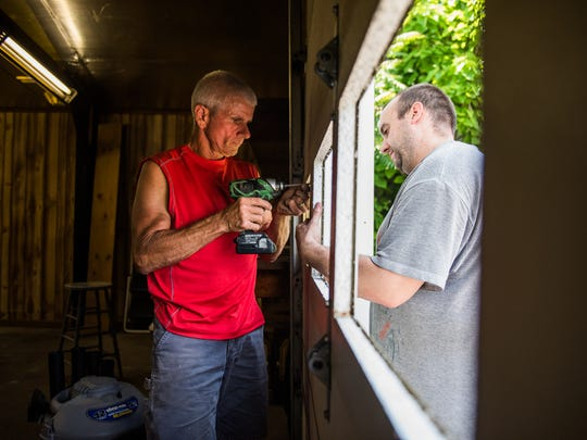 Jim Carbaugh, left, and Bryan Sharrow, right, work on replacing garage door windows at a warehouse on Carlisle Street in Hanover in June. The location will be used as a headquarters for Love LIVES, a non-profit organization in Hanover that is dedicated to helping victims of domestic abuse.