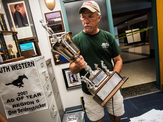 South Western School District athletic director Don Seidenstricker brings up the Hanover City Cup from its display case Wednesday July 13, 2016 at South Western High School.