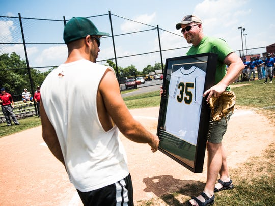 Keith Bevenour carries his retired New Oxford Twins jersey with Dan Shafer, left, after he was awarded the official retirement before New Oxford's game Saturday July 23, 2016 at New Oxford High School.