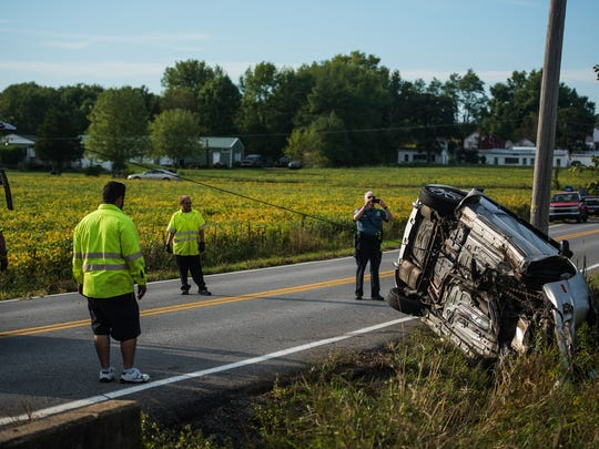 Emergency responders and tow company employees work at the scene of a single vehicle crash Sept. 21, 2016 in Latimore Township.