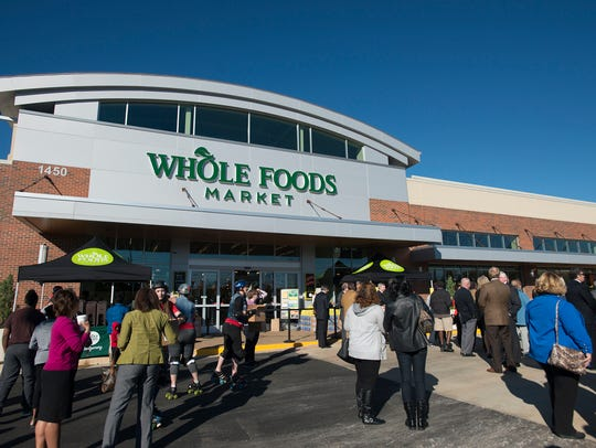 Shoppers wait outside the Montgomery Whole Foods store
