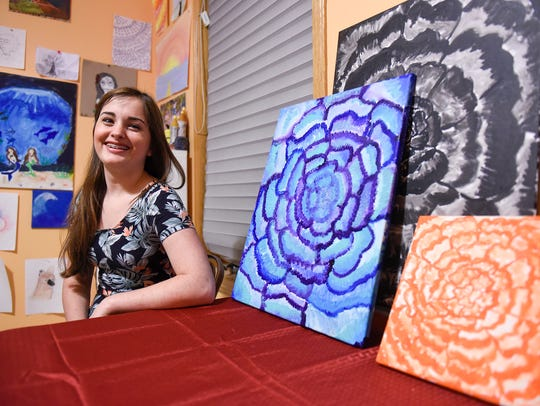 Grace Grell smiles with a collection of her paintings
