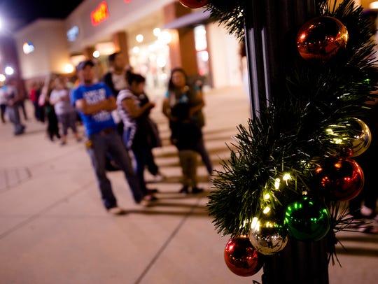 Shoppers wait outside Kohl's in Montgomery, Ala., on
