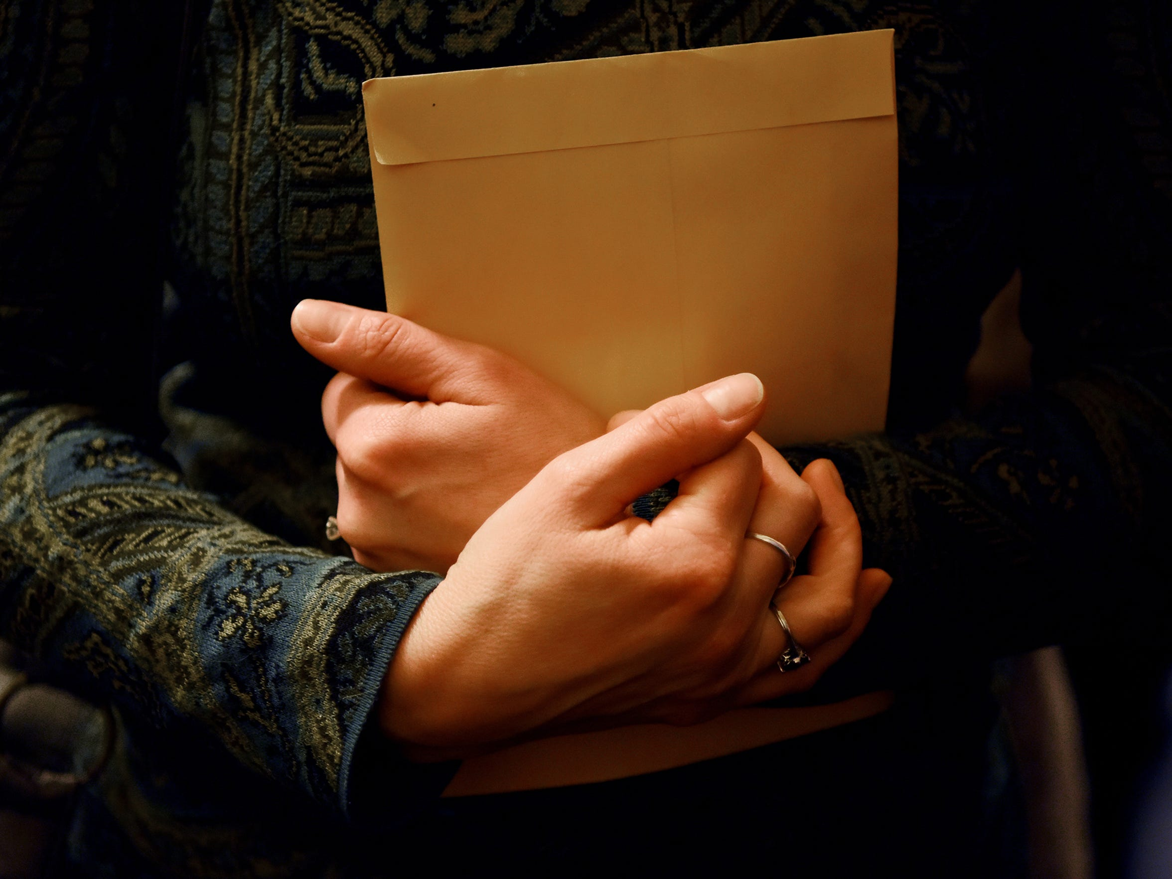 Adoptee Theresa Carroll of East Islip, NY clutches and envelope containing her just received birth certificate.