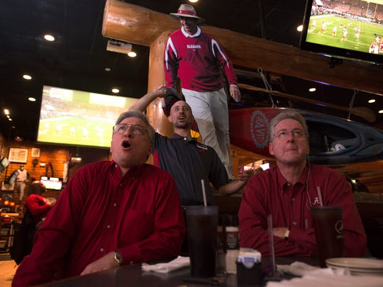 Troy Hughes, left, and Rickey Hollon cheer while watching the National Championship game at Baumhower's restaurant in Montgomery, Ala., on Monday, Jan. 9, 2017.