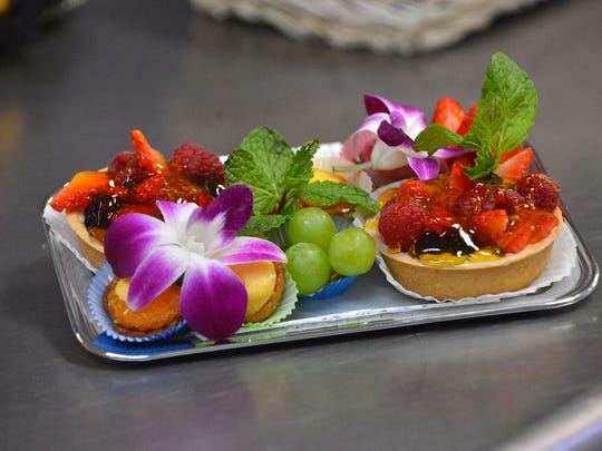 A colorful fruit tart tray ready to be wrapped up and delivered to a private plane.