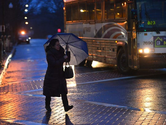 A woman shielding herself from the wind and rain as she crossed West Ridgewood Avenue in Ridgewood on Monday night.