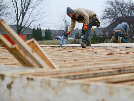 Josiah Schafer frames a home for Lane and Emily Bargeron in late January in St. Johns.