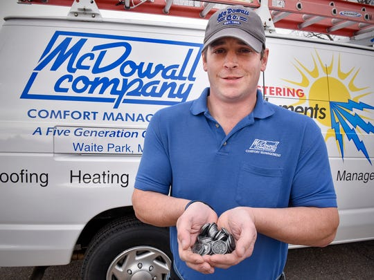Aaron Mesna holds a handful of the tokens in support of law enforcement officers that he hands out while traveling for his job with McDowall Companies.