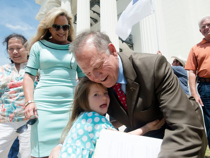 Roy Moore embraces Lydia Ford, 5, after announcing