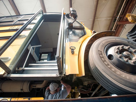 Mechanic Dwayne Stoddard works on pulling a transmission