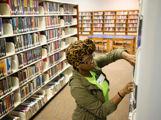 Tiffany Williams, 17, arranges books while working on Tuesday, June 6, 2017, at the Morgan Library in Montgomery, Ala.