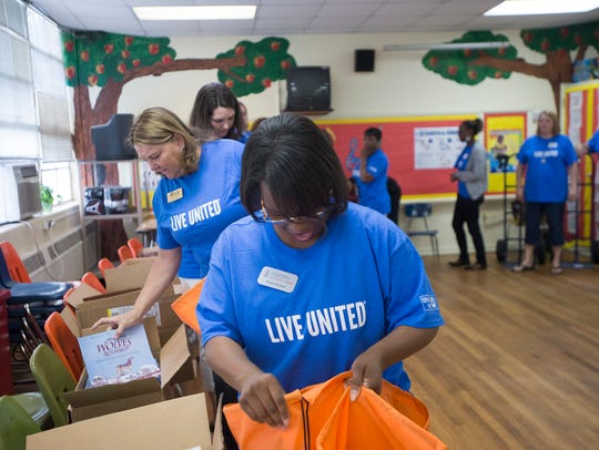 Kenya Howard, a United Way volunteer, puts books into