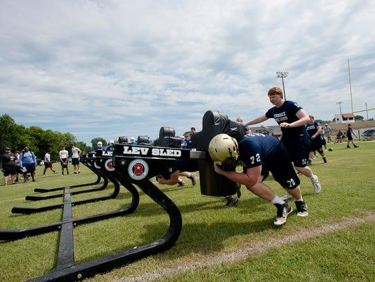 Catholic linebackers push a sled during the Alabama